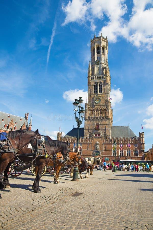 BRUGGE BELGIEN - JUNI 13, 2014: Vagnen på den Grote Markt och Belfort skåpbilen Brugge i bakgrund fotografering för bildbyråer