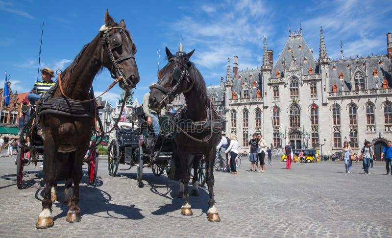 BRUGGE BELGIEN - JUNI 13, 2014: Vagnen på Groten Markt och den Provinciaal Hof byggnaden royaltyfri foto
