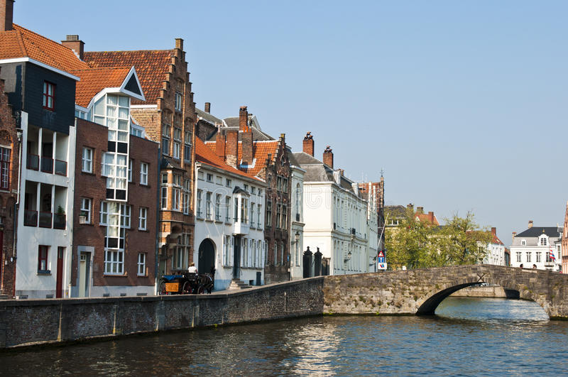 Brugge Belgium. View of some ancient houses and a canal with a bridge in the historical town of Brugge in Belgium. A horse-drawn cart is visible stock photo