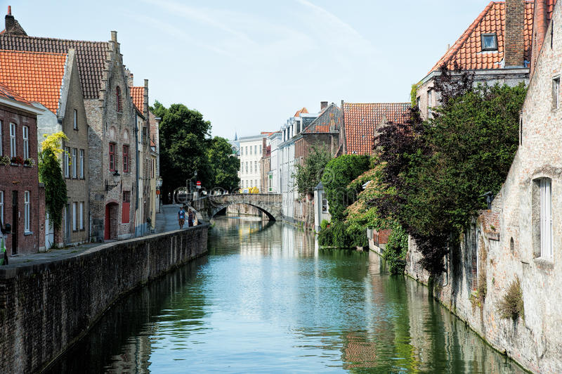 A Brugge canal. A canal through the centre of Brugge, Belgium, with an old bridge spanning over the canal stock photography