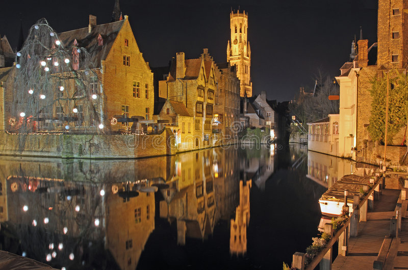 Brugge Downtown Canal At Night. Night time scene of center town buildings and belltower reflected in canal in Brugge, Belgium royalty free stock image