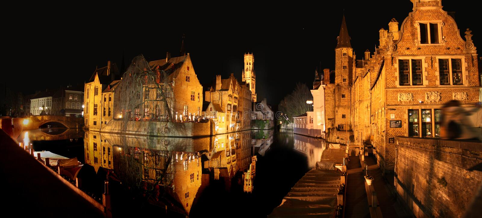 Brugge at night. Night scene of buildings and the main tower of the city Brugge (Belgium), all reflecting in a canal stock images
