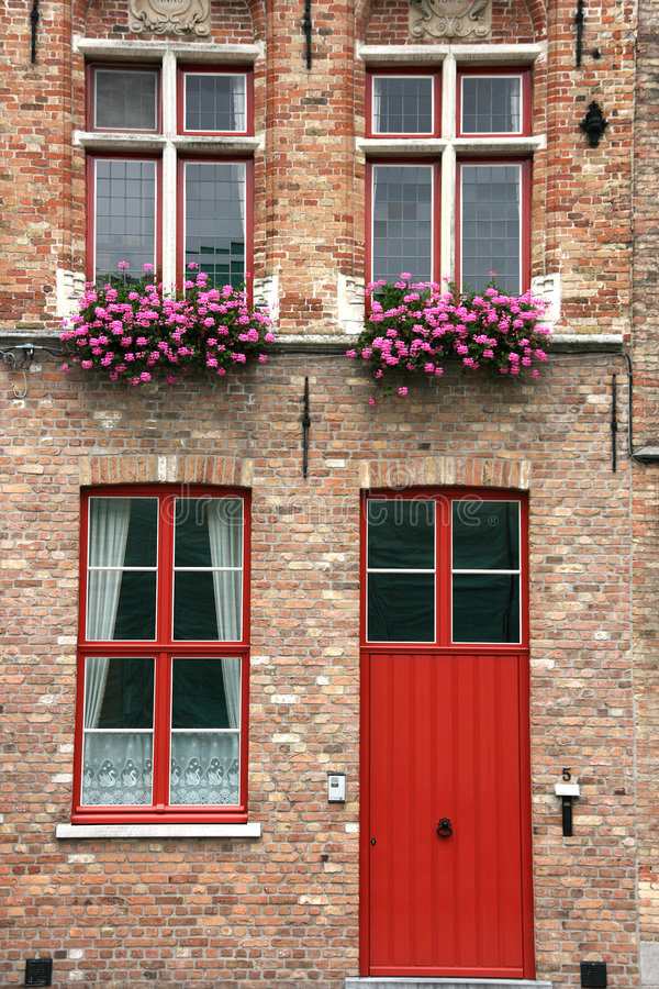 Brugge street. Brugge, Belgium. Old town building with red door and flowers in windows royalty free stock photo