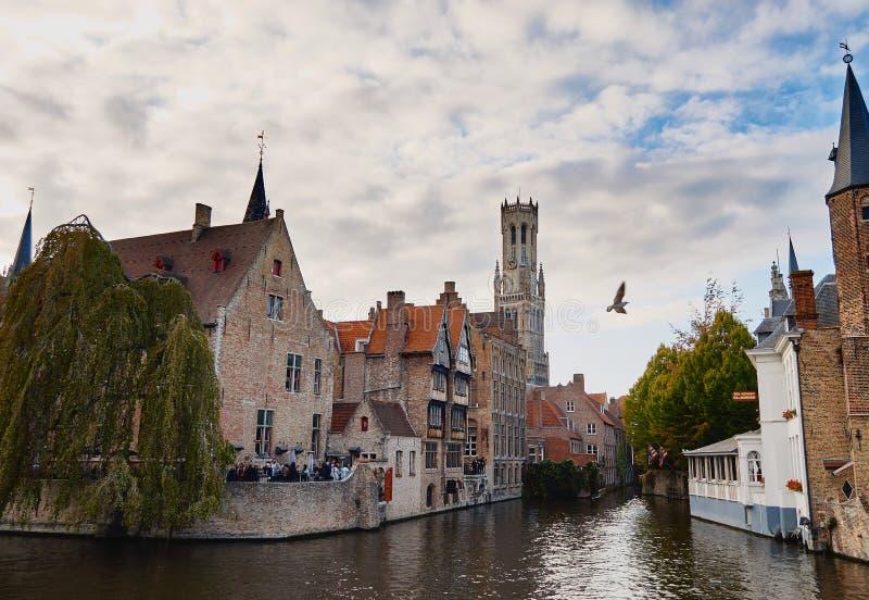 Brugge, West-Vlaanderen, België, 19 Oktober, 2018: Weergeven van middeleeuwse gebouwen, toren van Klokketoren en waterkanaal van  stock foto's