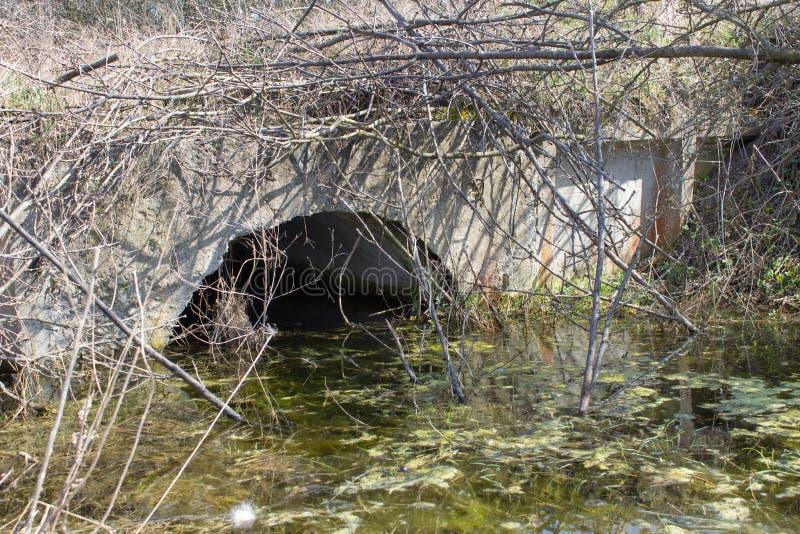Brugwatervervuiling, stagnerend vuil water dichtbij de steenbrug, ecologische ramp van water royalty-vrije stock afbeelding