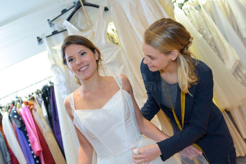 Bruid-aan-probeert op huwelijkskleding bij kledingsmontage royalty-vrije stock foto's