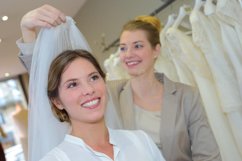 Bruid-aan-probeert op sluiers in de winkel van de huwelijkskleding stock afbeeldingen