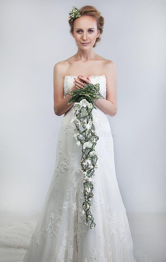 Bruid blond met boeket van bloemen royalty-vrije stock foto