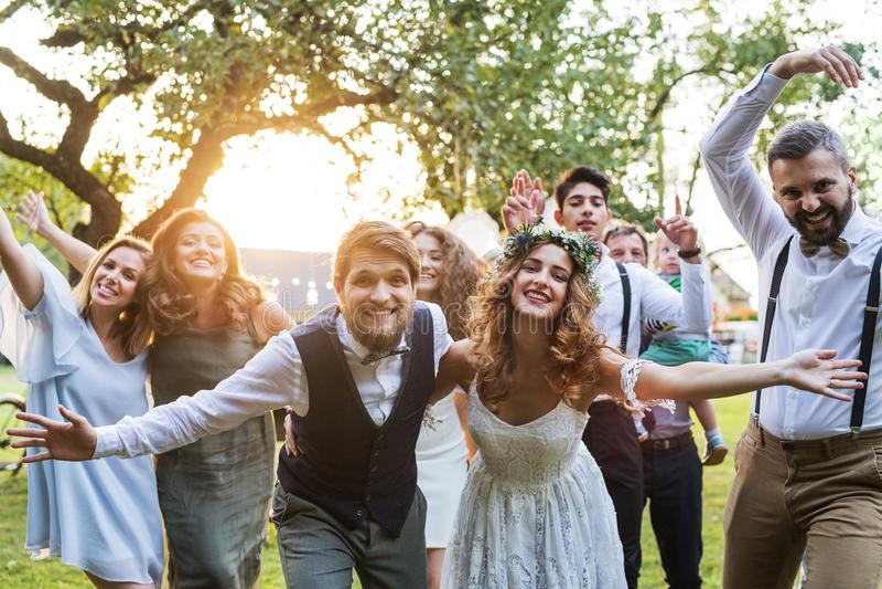 Bruid, bruidegom die, gasten voor de foto bij huwelijksontvangst buiten stellen in de binnenplaats stock fotografie