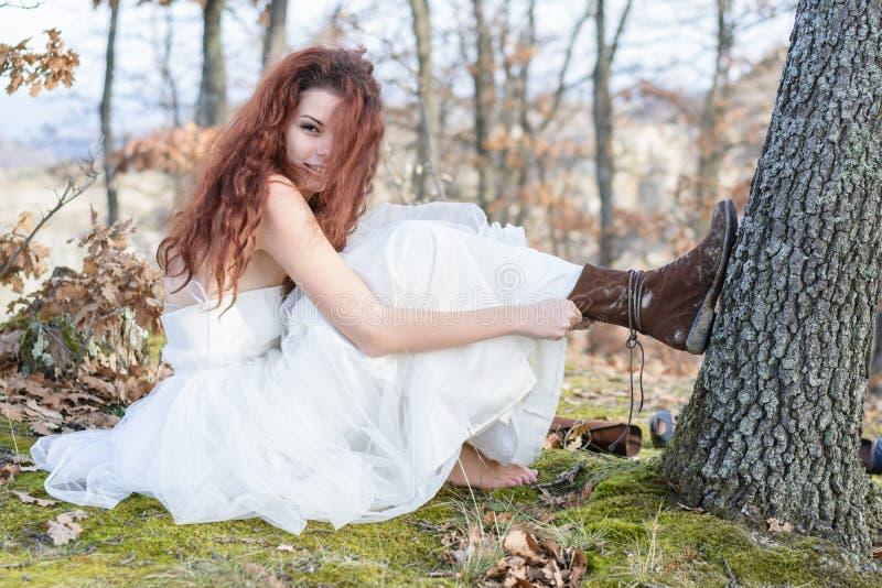 Bruid in de bos veranderende schoenen stock afbeeldingen