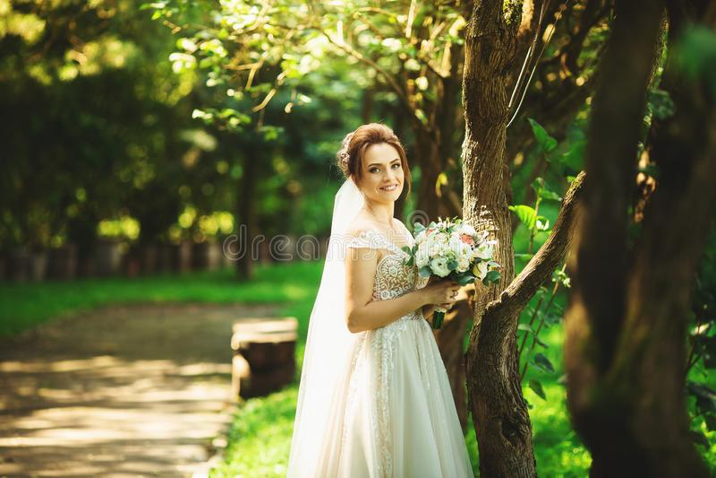 Bruid in de kleding van het manierhuwelijk op natuurlijke achtergrond Een mooi vrouwenportret in het park royalty-vrije stock foto
