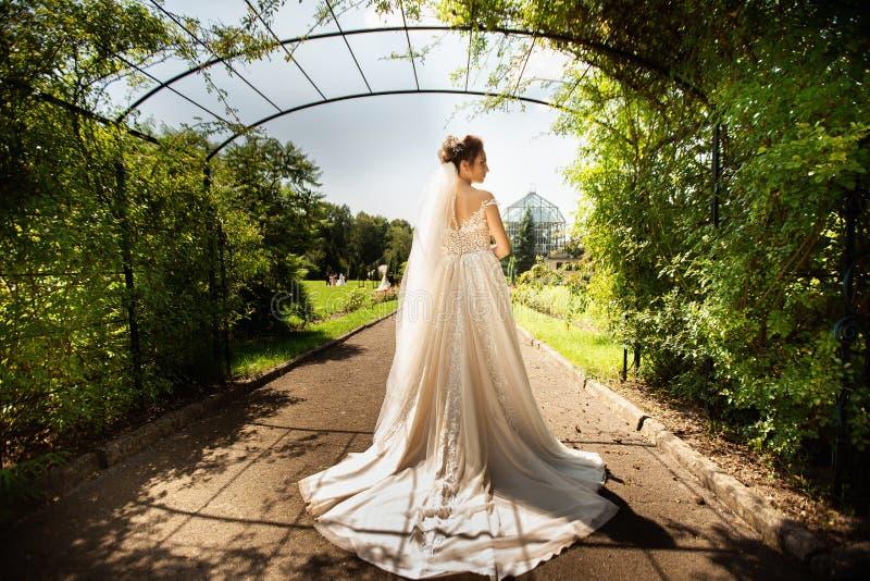 Bruid in de kleding van het manierhuwelijk op natuurlijke achtergrond Een mooi vrouwenportret in het park Achter mening stock foto
