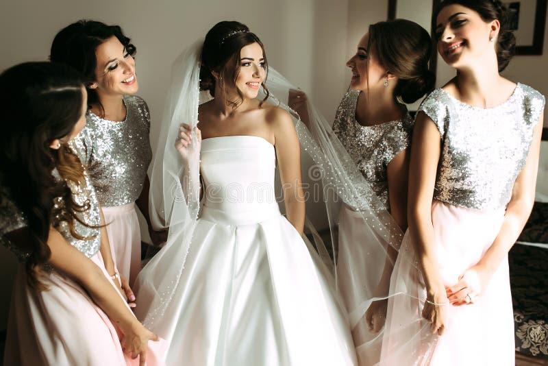 Bruid in de sluier door bruidsmeisjes wordt omringd dat stock afbeelding