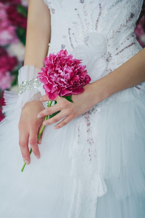 Bruid die de pioenbloem houden stock foto
