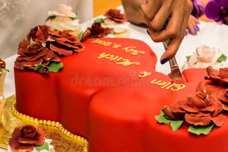 Bruid die de Rode Cake van het Fluweelhuwelijk snijden royalty-vrije stock afbeelding