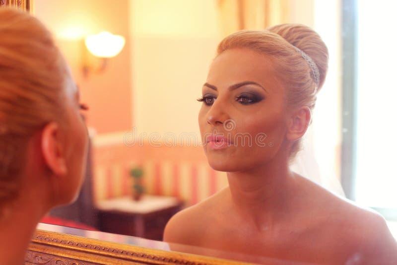 Bruid die in de spiegel kijken stock afbeelding
