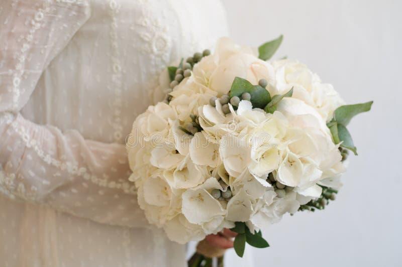 Bruid die een Kleurrijk Boeket van de Huwelijksbloem van Witte Hydrangea hortensia, Pioenen en Rozen houden royalty-vrije stock afbeeldingen