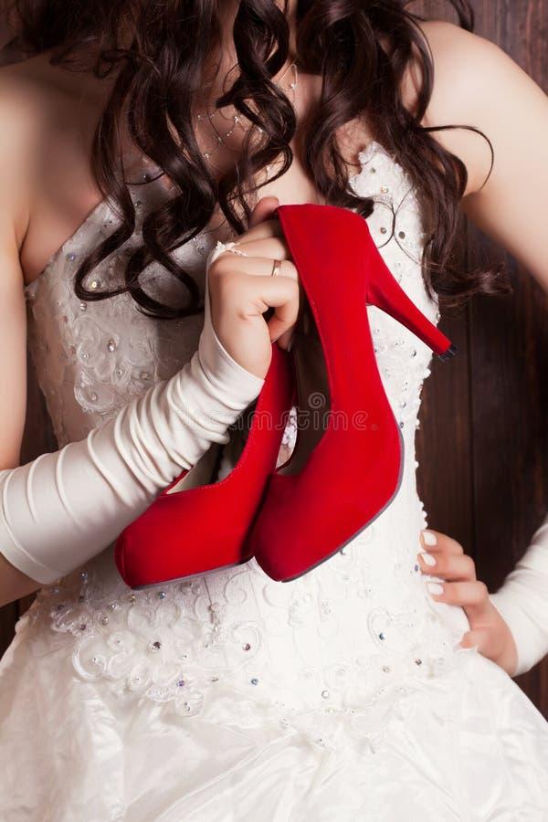 Bruid die een paar rode schoenen houden royalty-vrije stock foto