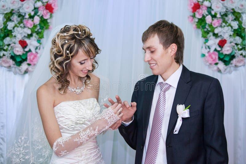 Bruid die een trouwring op de vinger van de bruidegom zet stock fotografie