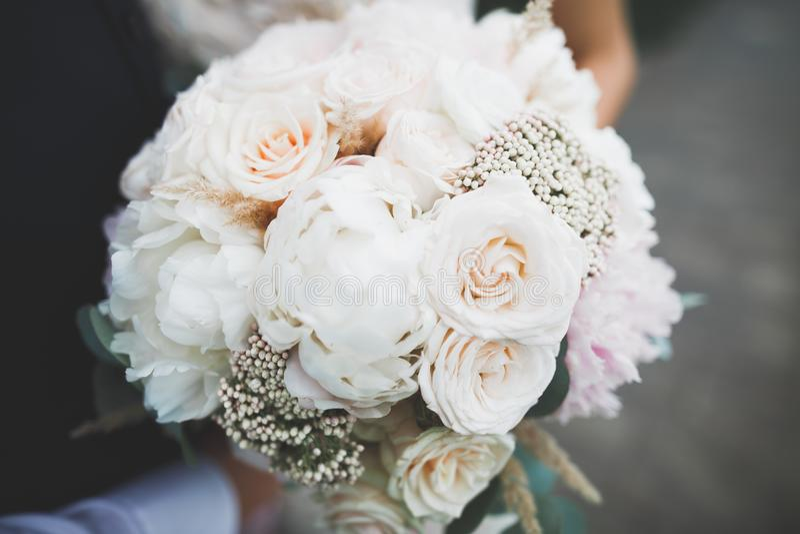 Bruid die groot en mooi huwelijksboeket met bloemen houden stock afbeelding