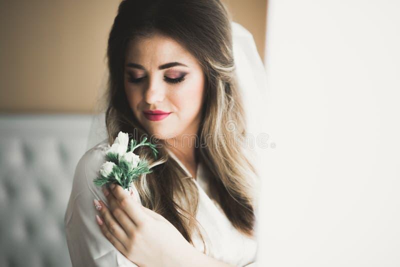 Bruid die groot en mooi huwelijksboeket met bloemen houden stock foto's