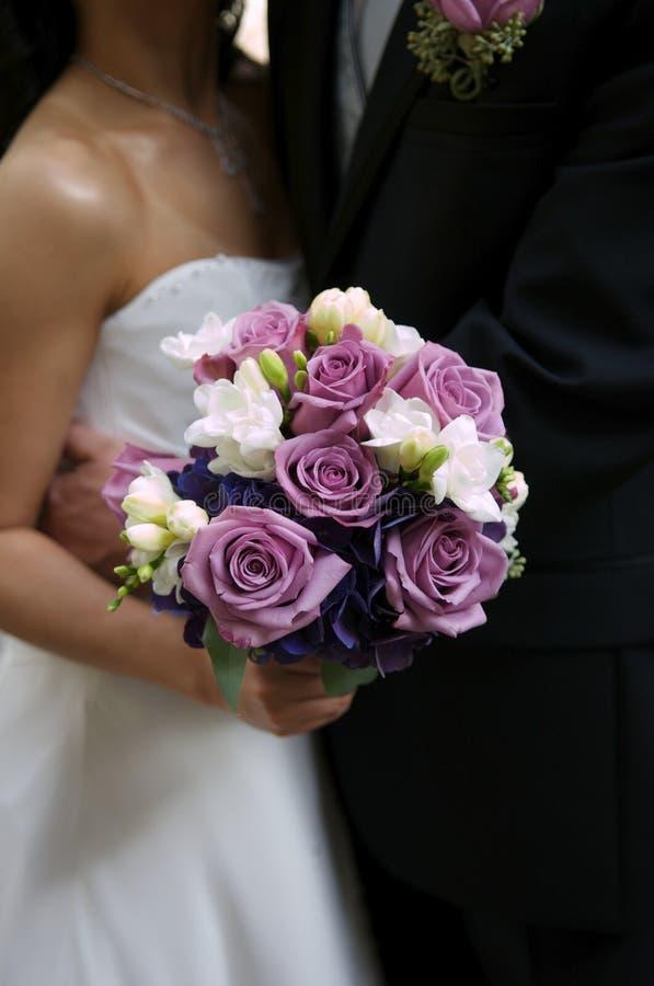 Bruid die haar boeket met bruidegom houdt stock foto's