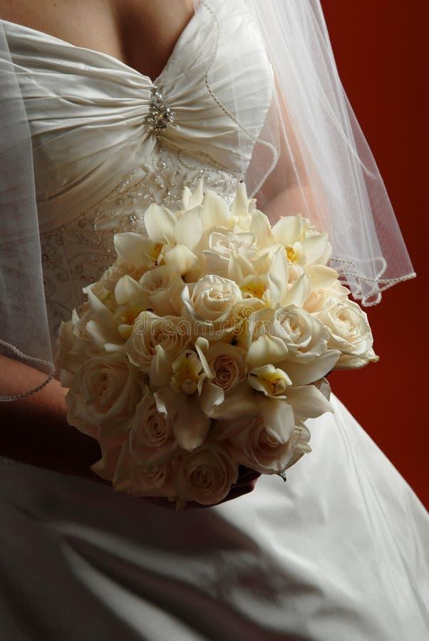 Bruid die haar bruids boeket houdt royalty-vrije stock afbeeldingen