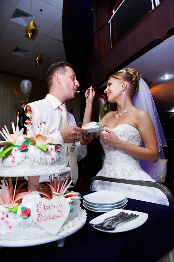 Bruid die haar cake van het fiancehuwelijk voedt stock foto