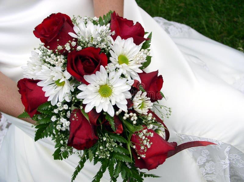 Bruid die haar huwelijksboeket houdt tegen haar kleding royalty-vrije stock foto's