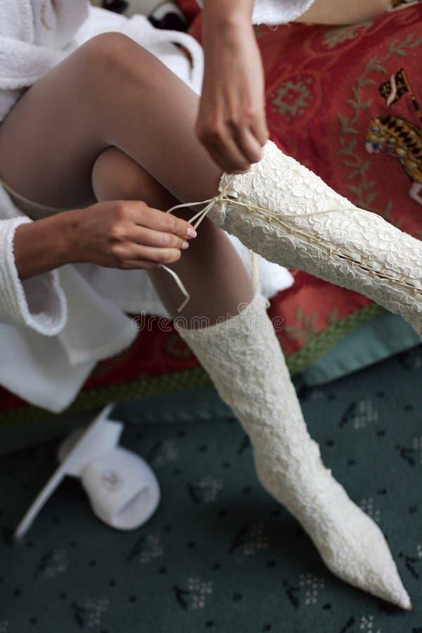 Bruid die haar laarskant bindt stock afbeelding