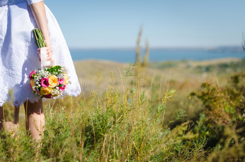 Bruid die helder huwelijksboeket houden stock foto's
