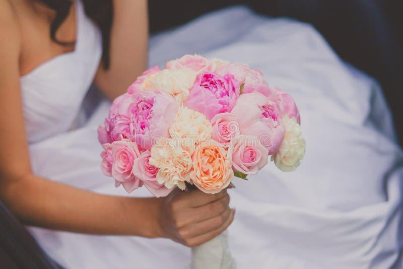Bruid die het heldere boeket van de huwelijkspioen houden royalty-vrije stock fotografie