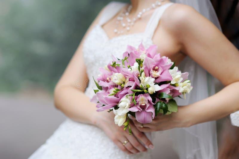Bruid die het roze boeket van huwelijksbloemen houdt stock fotografie