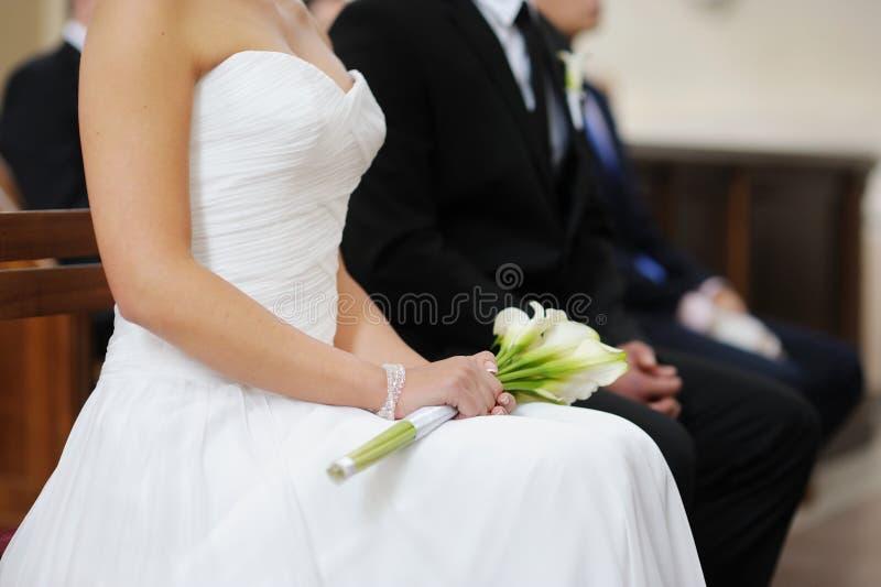 Bruid die het witte boeket van huwelijksbloemen houdt stock afbeelding