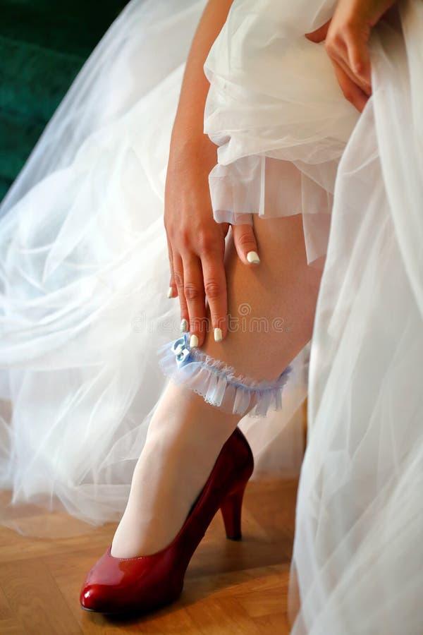Bruid die kouseband op huwelijksdag dragen stock foto's