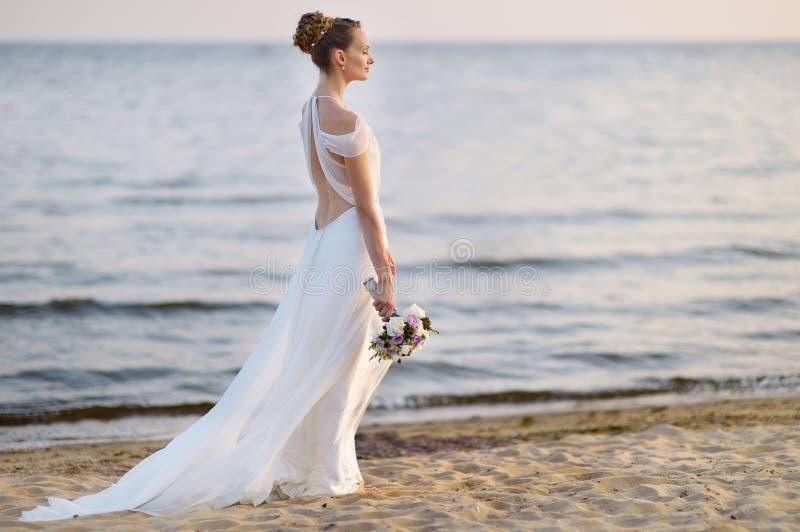 Bruid die langs overzeese kust in huwelijkskleding lopen stock afbeelding