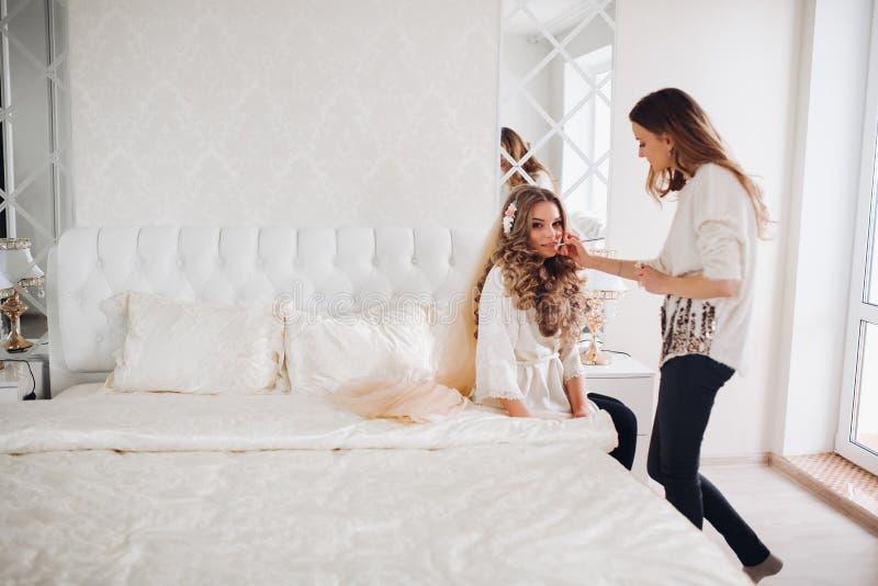 Bruid die make-up in de ochtend in een ruimte doen de grimeur die beroeps doen maakt omhoog van jonge vrouw Grimeur stock fotografie