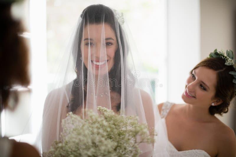 Bruid die met bloemboeket zich thuis bevinden royalty-vrije stock afbeelding