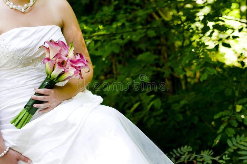 Bruid die met haar huwelijksboeket pronkt royalty-vrije stock afbeeldingen