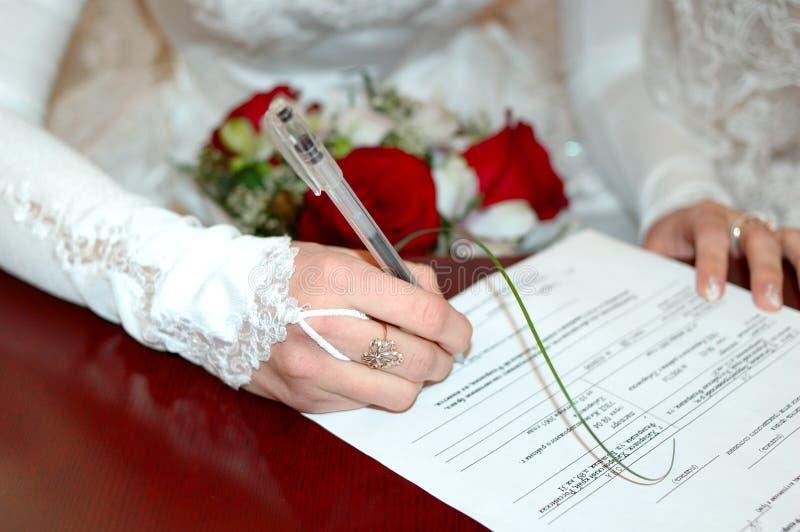 Bruid die met huwelijksboeket huwelijkslijnen ondertekent. stock afbeelding