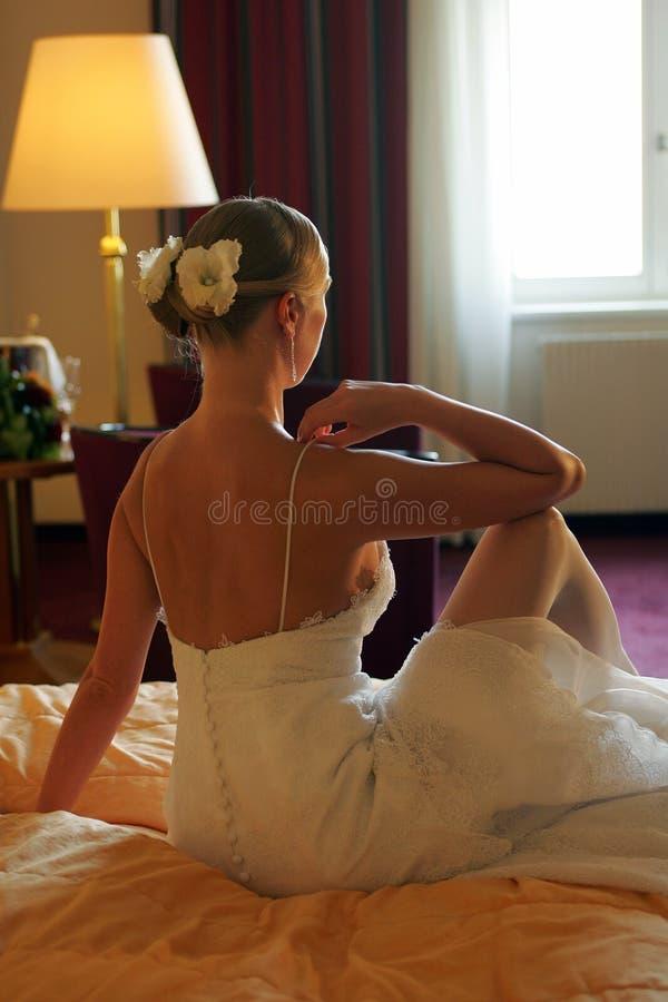 Bruid die op bed achtermening wordt gezeten royalty-vrije stock foto