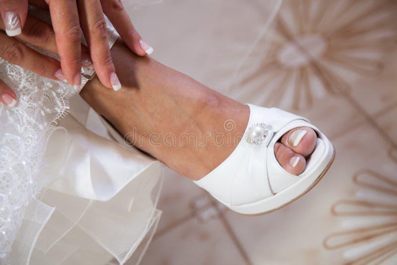 Bruid die op haar witte huwelijksschoenen zetten stock foto's