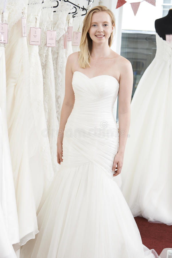 Bruid die op Huwelijkskleding proberen in Bruids Boutique royalty-vrije stock fotografie