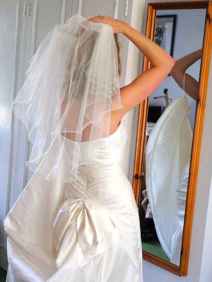 Bruid die op sluier zetten royalty-vrije stock afbeelding