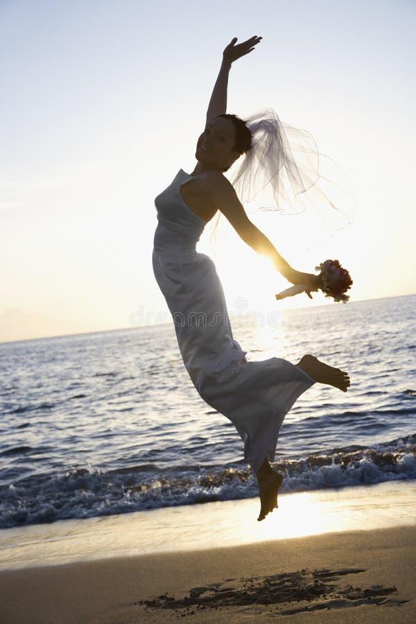 Bruid die op strand springt. stock afbeelding