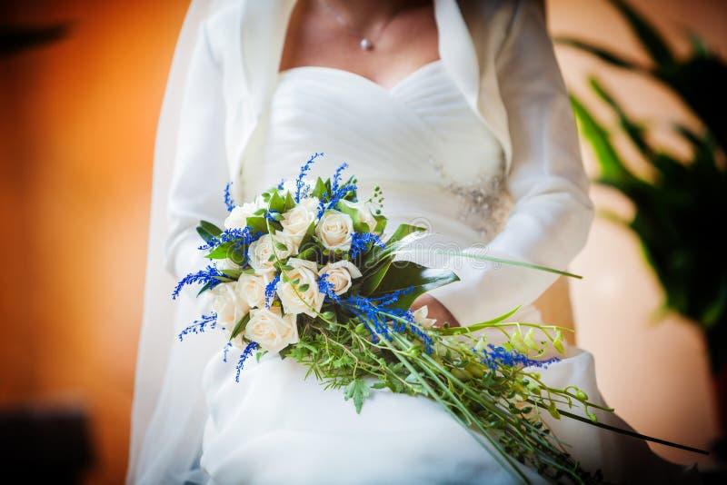 Bruid die rood rozenboeket houden stock afbeelding