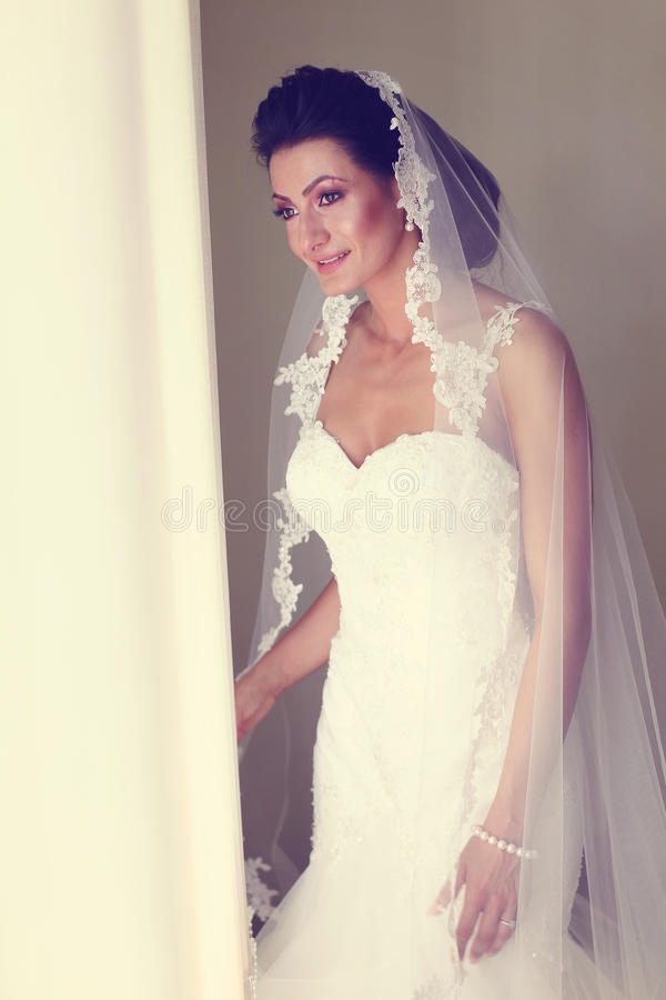 Bruid die van het venster kijken stock fotografie