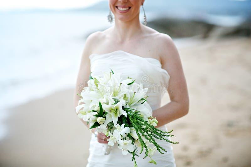 Bruid die wit huwelijksboeket houdt stock fotografie