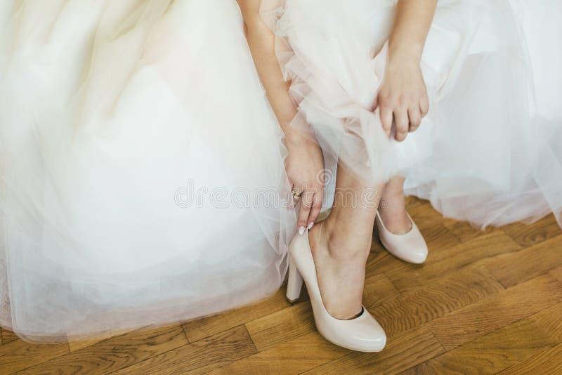 Bruid die witte huwelijkskleding en schoenen dragen royalty-vrije stock foto