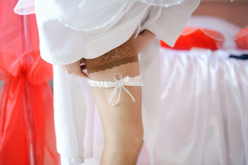 Bruid die witte kouseband op haar been aanpast stock foto's